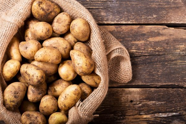 fresh potatoes in sack on wooden table, top view